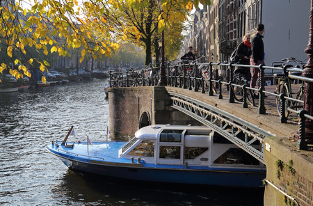 city park boat house: Amsterdam, The Netherlands - November 11, 2016: People walk on a bridge while a tour boat sails under the bridge over a canal with autumn trees in historical Amsterdam, The Netherlands on November 11, 2016