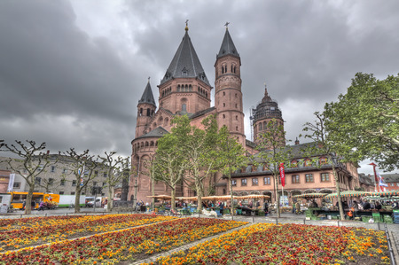Mainz, Germany - April 29, 2014: People shopping in the market on the central Marktplatz town square next to the cathedral seen across flowers in a small park in Mainz, Germany on April 29, 2014