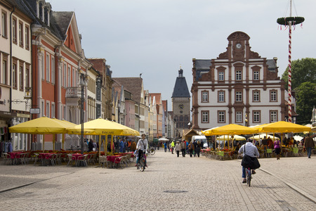 clocktower: Speyer, Germany - May 2, 2014: People walk and cycle in the mainstreet flanked with historical buildings, shops and the old clocktower in the old centre of Speyer, Germany on May 2, 2014