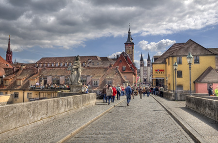 Wurzburg, Germany - May 4, 2014: People cross the old Main Bridge toward the center of town in Wurzburg, Germany on May 4, 2014 Editorial
