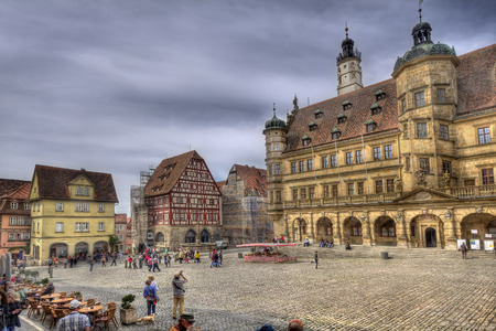 Rothenburg ob der Tauber, Germany - May 6, 2014: People walk on the medieval town square with city hall of Rothenburg ob der Tauber on May, Germany on May 6, 2014.