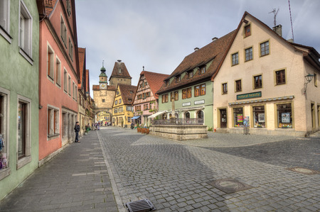 fachwerk: Rothenburg ob der Tauber, Germany - May 6, 2014: Historical street with people admiring the medieval architecture of houses and a clock tower gate in Rothenburg ob der Tauber, Germany on May 6, 2014.
