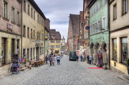 fachwerk: Rothenburg ob der Tauber, Germany - May 6, 2014: Historical street with people admiring the medieval architecture of houses and shops and a clock tower gate in Rothenburg ob der Tauber, Germany on May 6, 2014.