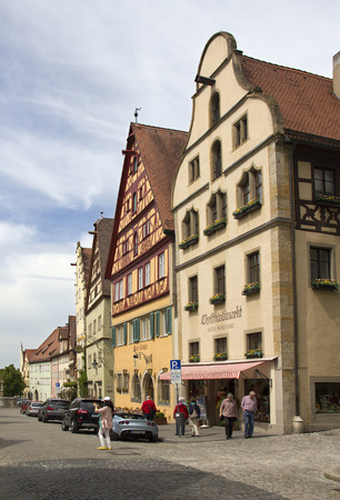 Rothenburg ob der Tauber, Germany - May 6, 2014: Historical street with people admiring the medieval architecture of houses and shops in Rothenburg ob der Tauber, Germany on May 6, 2014.
