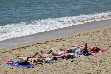 suntanning: Barcelona, Spain - May 23, 2015: Girls lie suntanning on the beach in Barcelona, Spain on May 23, 2015.