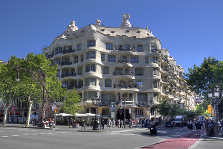 traffic building: Barcelona, Spain - May 22, 2015: People and traffic in front of the famous Casa Mila, or La Pedrera building by the Catalan architect Gaudi in Barcelona, Spain on May 22, 2015. Editorial