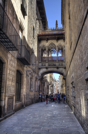 Barcelona, Spain - May 22, 2015: A group of schoolchildren under the bridge in Del Bisbe street in the Gothic Quarter in downtown Barcelona, Spain on May 22, 2015.