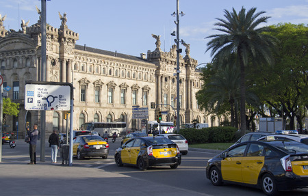 traffic building: Barcelona, Spain - May 21, 2015: Taxi cabs and other traffic near the old customs building in Barceloneta, the harbor of Barcelona, Spain on May 21, 2015.