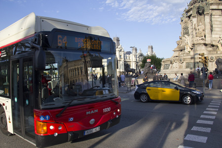 Barcelona, Spain - May 21, 2015: City bus with reflection of buildings and taxi cab in Barceloneta, the harbor of Barcelona, Spain on May 21, 2015. Editorial