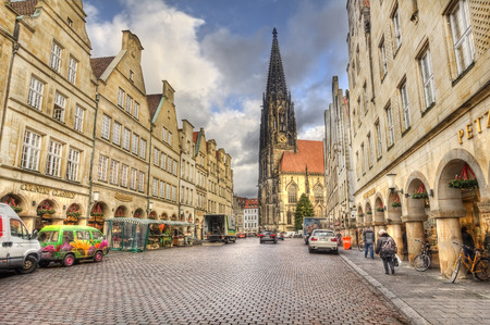 sain: Munster, Germany - December 23, 2015: People walk in the early morning in the Prinzipalmarkt street lined with historical buildings and the Saint Lamberti church and a chrismas tree in Munster, Germany on December 23, 2015 Editorial
