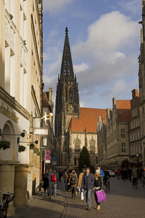 sain: Munster, Germany - December 23, 2015: People with shopping bags walk in the Prinzipalmarkt street lined with shops in historical buildings and the Saint Lamberti church and a chrismas tree in Munster, Germany on December 23, 2015 Editorial
