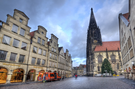 sain: Munster, Germany - December 23, 2015: People cycle in the early morning in the Prinzipalmarkt street lined with historical buildings and the Saint Lamberti church and a chrismas tree in Munster, Germany on December 23, 2015