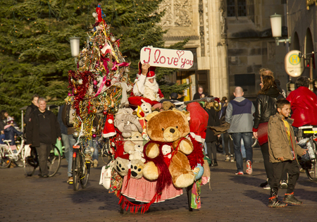 munster: Munster, Germany - December 23, 2015: Man on bicycle dressed as Santa Claus holding a sign I love you on the Prinzipalmarkt street in Munster, Germany on December 23, 2015