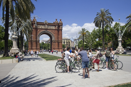 Barcelona, Spain - May 23, 2015: Tourists on bicylces take pictures in front of the Arc de Triomf triumphal arch in Barcelona, Spain on May 23, 2015.
