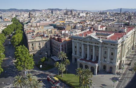 View from the memorial column for Columbus of large buildings along the Rambla street and boulevard in the city of Barcelona, Spain