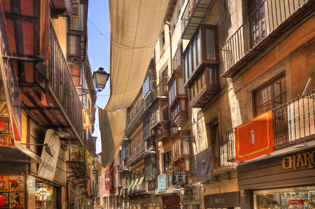 Toledo, Spain - June 1, 2016: Shops and other buildings in a historical street in central Toledo, Spain on June 1, 2016