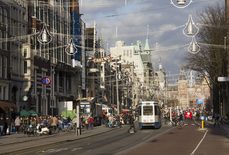 Amsterdam, Holland - November 12, 2015: People waiting at a street car stop in a major shopping street decorated for Christmas, with the railway station in the distance, on November 12, 2015 in Amsterdam, Holland. Editorial