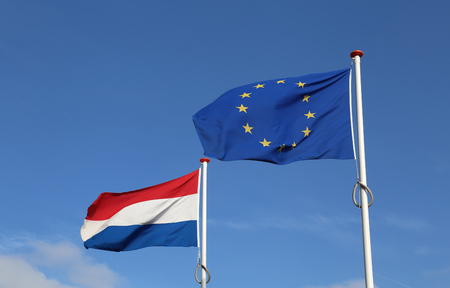 Dutch and European Union Flag waving against a blue sky in The Hague, Holland Stock Photo