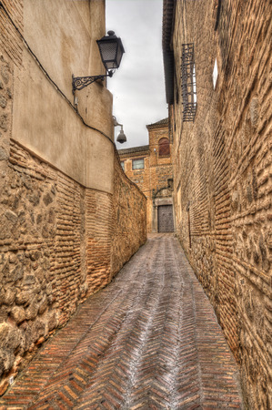 Narrow alley with traditional streetlight in the old town of Toledo, Spain