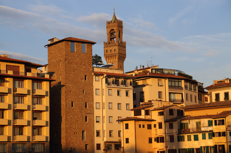 Historical buildings and the tower of the city hall Palazzo Vecchio behind the Ponte Vecchio bridge in the evening sun in Florence, Italy Фото со стока
