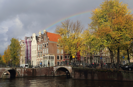Rainbow in cloudy sky above trees on a canal in autumn in Amsterdam, Holland Stockfoto