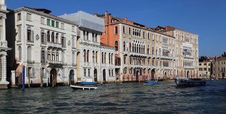 Facades of historical buildings with ornamental windows and balconies and a speedboat on the Grand Canal in Venice, Italy