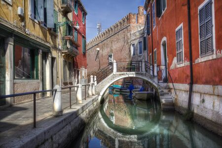 Small bridge across a canal along the wall of the arsenal and historical houses in Venice, Italy