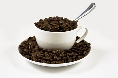 A white coffee cup on a whit background full of coffeee beans