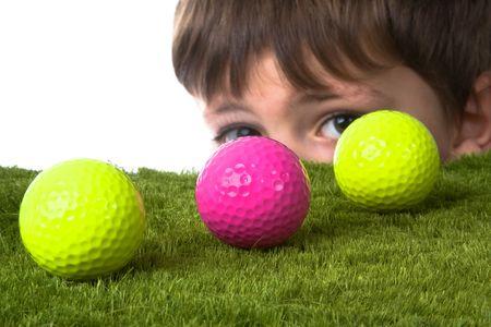 peaking: Boy peaking around a golf ball