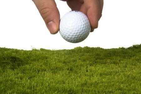 白い背景を持つ草にゴルフボールを置く男性製造業 写真素材