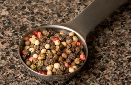measuring spoon: Measuring spoon with pepper corns in it. Stock Photo