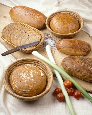 Various baked goods accompanied with leeks and tomatoes photo