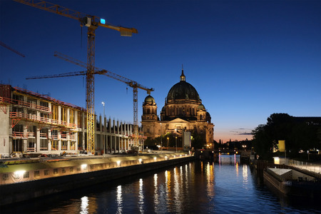 ongoing: Berlin cathedral overshadowed by ongoing construction with twilight skies reflecting in the Spree river.