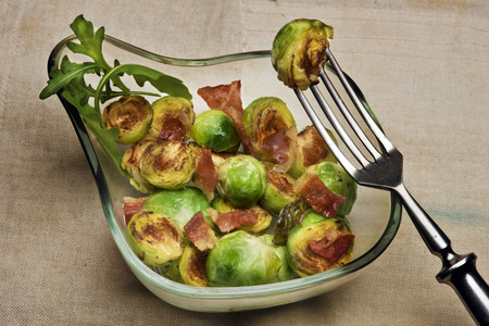 Grilled buttered Brussels sprouts with bacon in a glass bowl photo