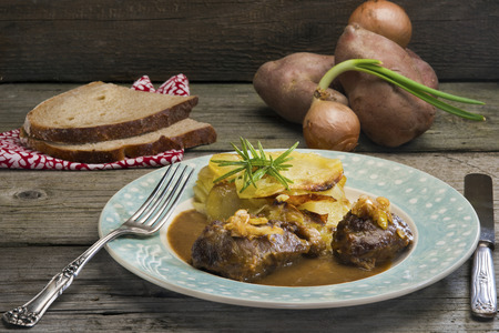 Welsh comfort food at its finest: Braised pork cheeks in gravy with cider caramelized leeks and onion cake - layers of sliced potatoes and soft rosemary scented onions (Welsh version of gratin dauphinois).