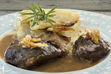 uk cuisine: Welsh comfort food at its finest: Braised pork cheeks in gravy with cider caramelized leeks and onion cake - layers of sliced potatoes and soft rosemary scented onions (Welsh version of gratin dauphinois).