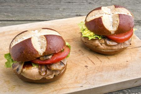 lye: Grilled pork steak sandwich (burger) with mushrooms in pretzel style lye roll
