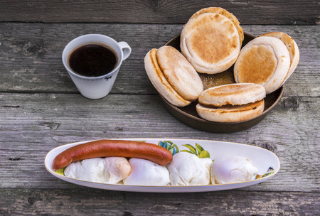 viennese: Protein rich breakfast with four eggs Benedict and Viennese sausage with toasted muffins and a cup of coffee.