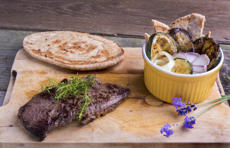 Provencal style horse meat entrecote steak with ratatouille and flat bread served on a wooden board decorated with lavender and fresh thyme. Imagens