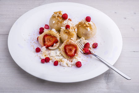 quark: Strawberries wrapped in quark based dough, served with crumbled quark, melted butter, forrest strawberries, brown sugar and finely grated gingerbread. Stock Photo