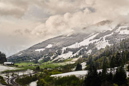 View on grassy meadows with melting snow and snowy mountains in Gastein valley in spring one cloudy day where leads road and railway from place near north entrance to valley