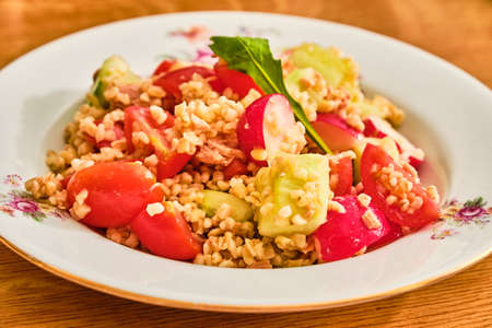 Tasty bulgur salad with tuna, radish, tomato and cucumber on white plate on wooden table