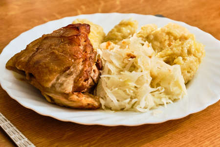 Traditional czech tasty roast pork knuckle meat - roasted pork knee - with furry dumplings - hairy dumplings - and cabbage on white plate on wooden table with serving 免版税图像