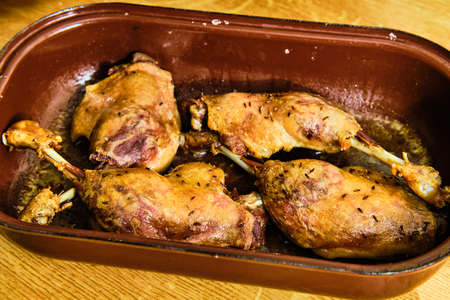 Roasted tasty duck lengs in metal cooking pan on wooden table