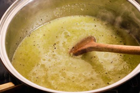 Mixed zucchini in broth with wooden spatula on cooking pan preparing tasty homemade soup