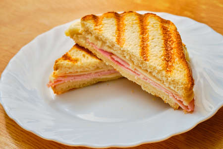 Tasty sliced toast with ham and cheese on white plate