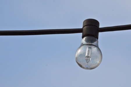 Bulb on the wire  with blue sky as background photo