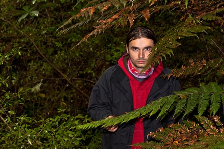 A dangerous looking man hidden in a dark forest Stock Photo - 8775584