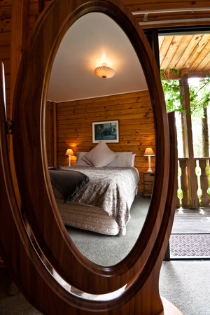 fox glacier: Nice warm bedroom interior of mountain lodge reflected in mirror. Fox Glacier Lodge, Fox Glacier, West Coast, South Island, New Zealand. Stock Photo