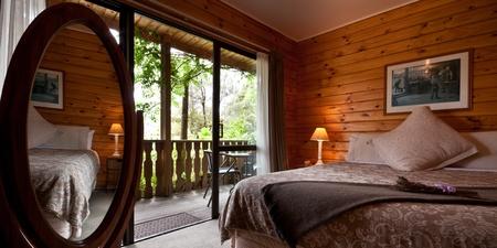 hospedaje: Interior dormitorio cálido agradable de albergue de montaña con terraza y reflejo en el espejo. Fox glaciar Lodge, Fox Glacier, Costa Oeste, Isla Sur, Nueva Zelanda.
